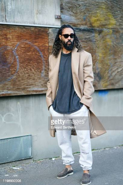 Jerry Lorenzo wears sunglasses a beige long coat a gray tshirt white Essential Fear of God sportswear pants suede gray shoes outside Marni during...