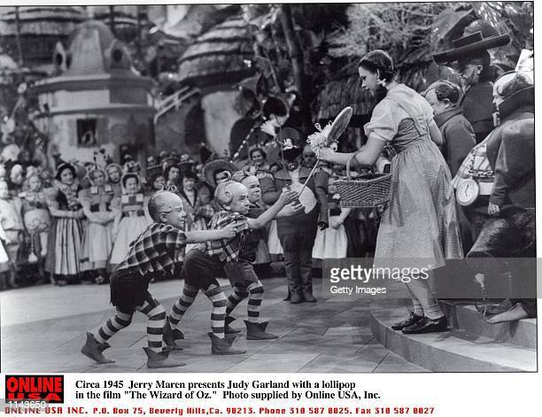 Jerry Maren playing a Lollipop Guild Member presents Judy Garland with a lollipop in the film The Wizard of Oz