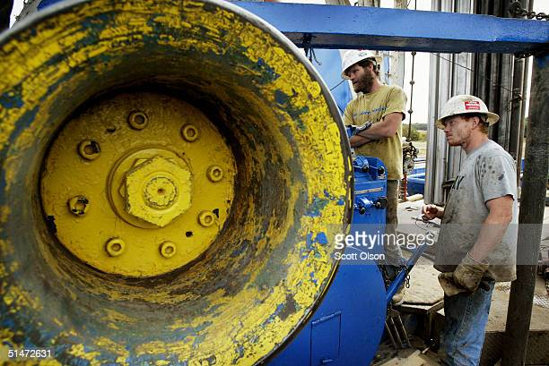 Jerry McKinney and Jeremy Beck work a drilling rig as they search for oil for Houston Texas based Vintage Exploration in a corn field October 9 2004...