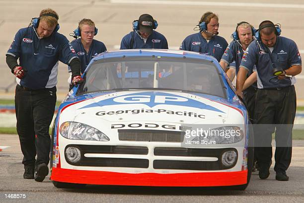 Jerry Nadeau driver of the Petty Enterprises Dodge Intrepid R/T is pushed into the garage by pit crew members during practice for the EA Sports 500...