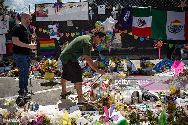 Jerry Perez center puts a rose on a photo of Jean Carlos Mendez Perez one of the victims killed one month ago at a memorial in front of Pulse...