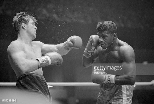 Jerry Quarry takes a swing at Floyd Patterson during their heavyweight bout. Quarry defeated Patterson after 12 rounds.