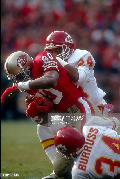 Jerry Rice of the San Francisco 49ers gets tackled by JC Pearson and Lloyd Burruss of the Kansas City Chiefs during an NFL football game December 24...