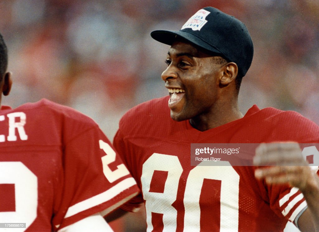 Jerry Rice #80 of the San Francisco 49ers laughs on the sidelines during the 1990 Super Bowl XXIV against the Denver Broncos on January 28, 1990 at the Louisiana Superdome in New Orleans, Louisiana. The 49ers defeated the Broncos 55-10.