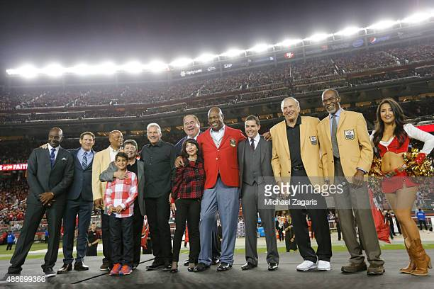 Jerry Rice Steve Young Ronnie Lott Eddie DeBartolo Joe Montana George Veras Denise York Charles Haley Jed York and Dave Wilcox sand on the field at...