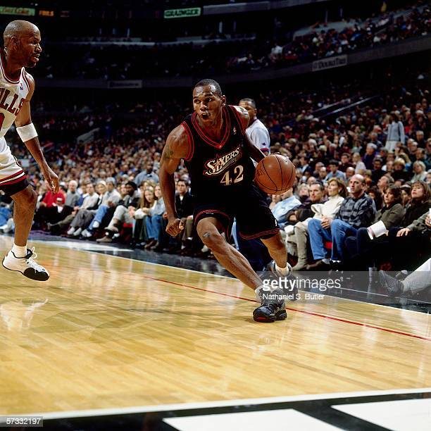 Jerry Stackhouse of the Philadelphia 76ers drives against Ron Harper of the Chicago Bulls during a game at United Center on November 1 1997 in...