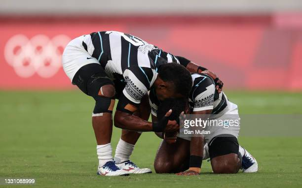 Jerry Tuwai of Team Fiji and Napolioni Bolaca of Team Fiji react on the final whistle following victory in the Rugby Sevens Men's Gold Medal match...