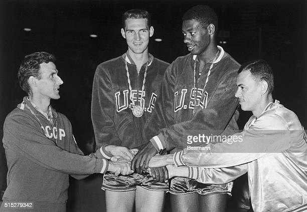 Jerry West and teammate Oscar Robertson representing the USA basketball players in the Rome Olympics are congratulated by a representative from...