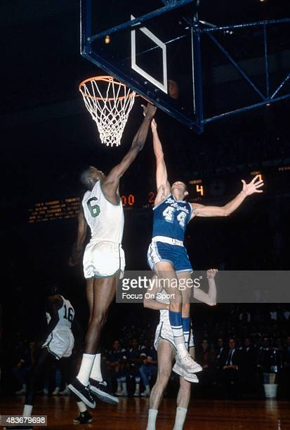 Jerry West of the Los Angeles Lakers goes up in an attempt to get his shot over the out stretch arm of Bill Russell of the Boston Celtics during an...