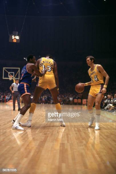 Jerry West of the Los Angeles Lakers moves the ball behind a screen set by teammate Wilt Chamberlain against the New York Knicks during a 1971 NBA...