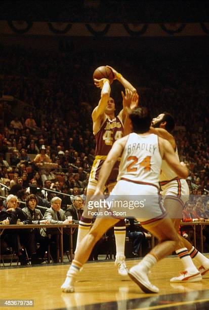 Jerry West of the Los Angeles Lakers shoots over Walt Frazier and Bill Bradley of the New York Knicks during an NBA basketball game circa 1969 at...