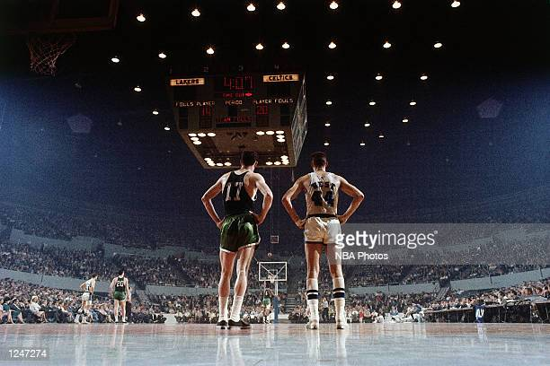 Jerry West of the Los Angeles Lakers stands next to John Havlicek of the Boston Celtics with a break in the action during an NBA game at the Forum in...