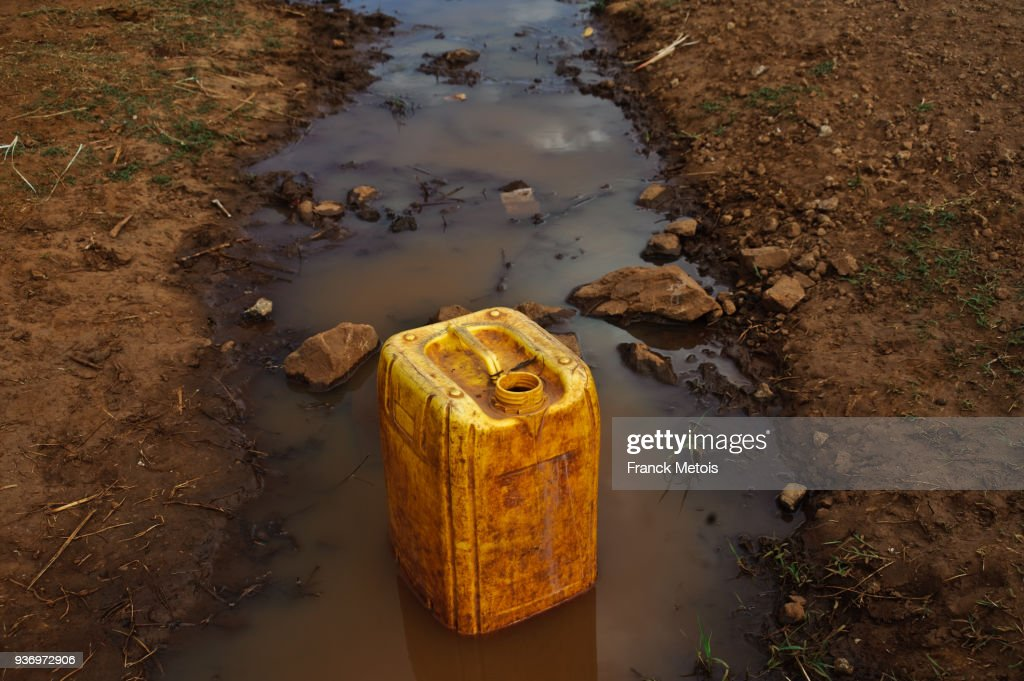 Jerrycan filled with water from the dirty trough ( Ethiopia) : Stock Photo