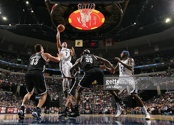Jerryd Bayless of the Memphis Grizzlies shoots against Kris Humphries and Reggie Evans of the Brooklyn Nets on January 25 2013 at FedExForum in...