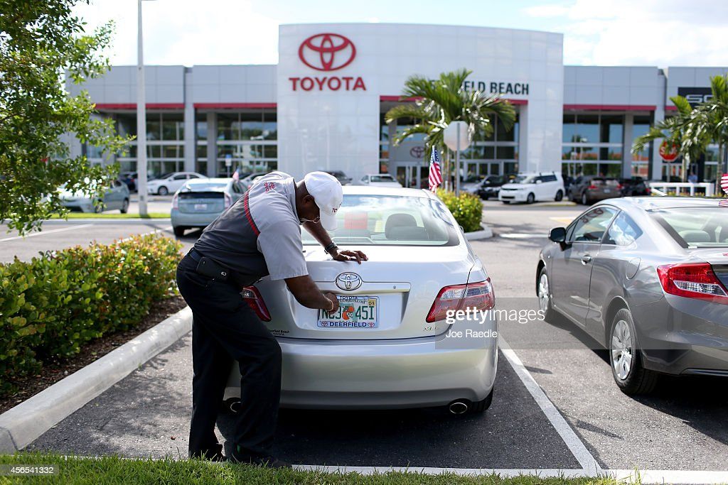 Jerryl Harden places a license plate on a vehicle at the