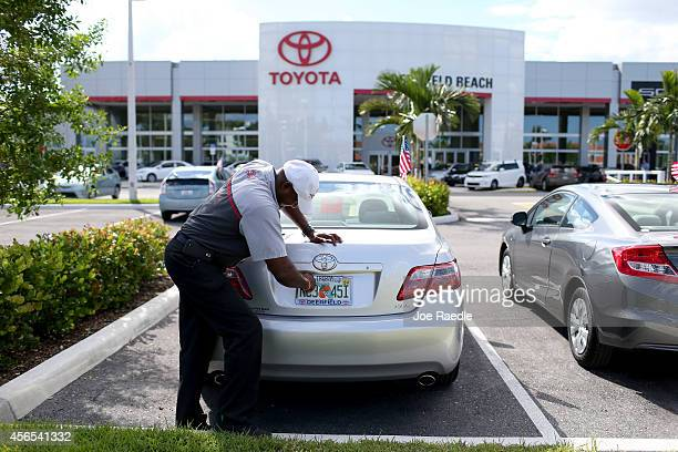 Jerryl Harden places a license plate on a vehicle at the Toyota of Deerfield dealership on the day that Warren Buffett's Berkshire Hathaway announced...