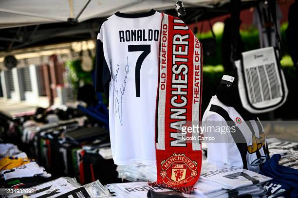Jersey bearing the name of Cristiano Ronaldo is displayed next to a Manchester United FC scarf at a stall outside Allianz Stadium. Cristiano Ronaldo...