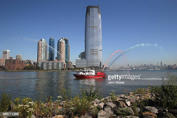 Jersey City firemen spray red white and blue water into the air as immigrants take part in a naturalization ceremony at Liberty State Park on...