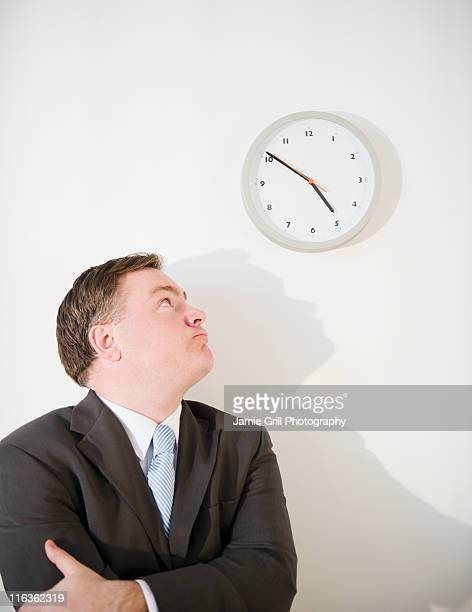 USA, Jersey City, New Jersey, businessman looking up at clock