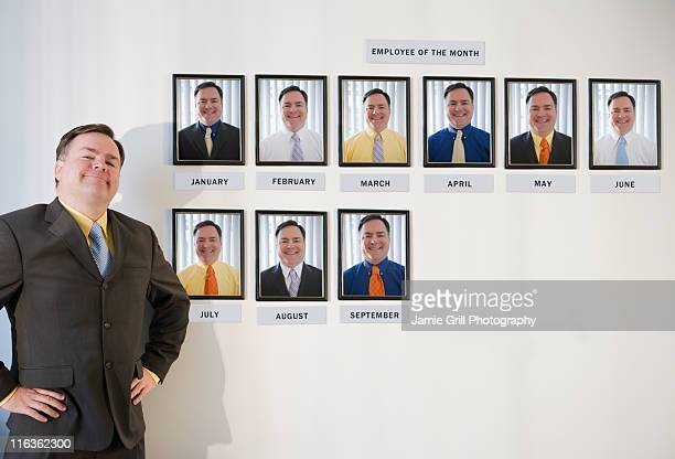 USA, Jersey City, New Jersey, businessman standing in front of employee of the month portraits