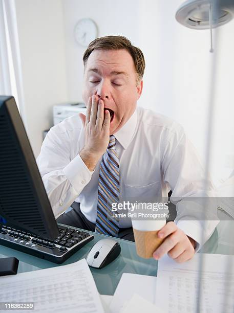 USA, Jersey City, New Jersey, businessman yawning in office