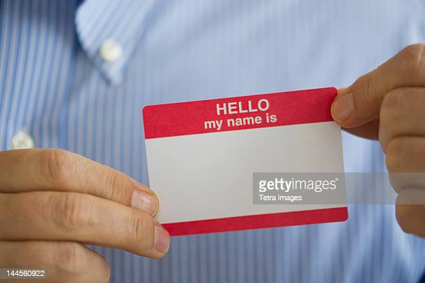 jersey city, new jersey, close up of businessman's hands holding  blank name tag, studio shot - name tag stock photos and pictures