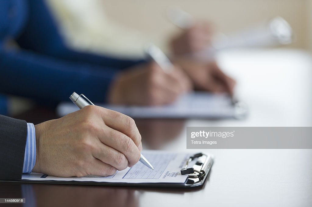 Jersey City, New Jersey, Close up of man's hands filling application form : Stock Photo