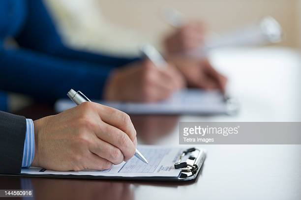 jersey city, new jersey, close up of man's hands filling application form - human body part stock pictures, royalty-free photos & images