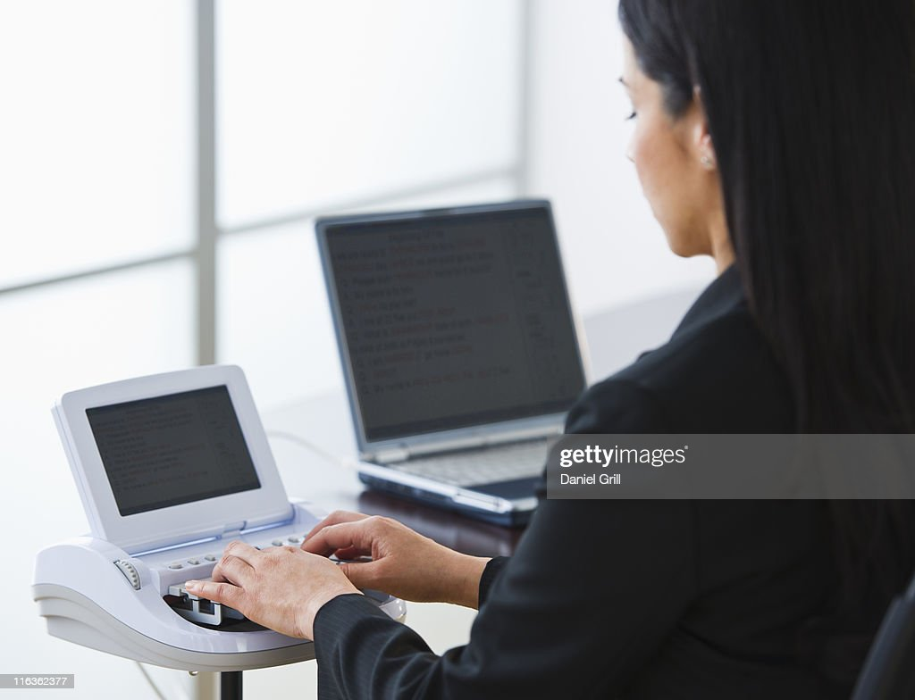 USA, Jersey City, New Jersey, court stenographer using stenograph machine : Stock Photo