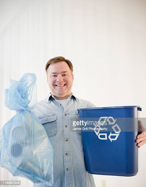USA, Jersey City, New Jersey, man holding bag and recycling bin