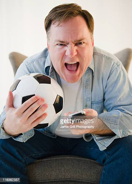 USA, Jersey City, New Jersey, man holding remote control and soccer ball