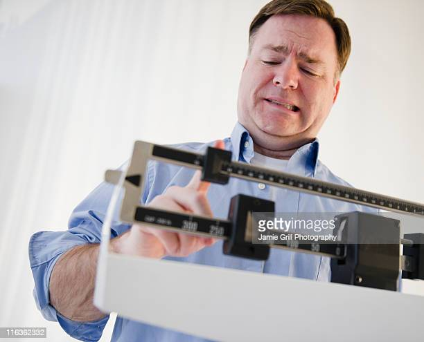 usa, jersey city, new jersey, man on weight scales - one man only stock pictures, royalty-free photos & images