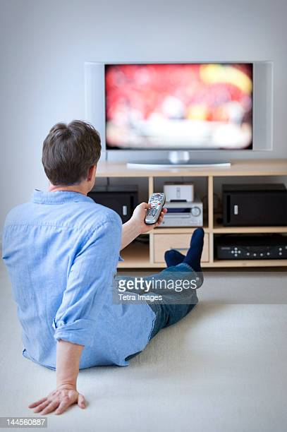 jersey city, new jersey, man watching tv in living room - sitting on ground stock pictures, royalty-free photos & images