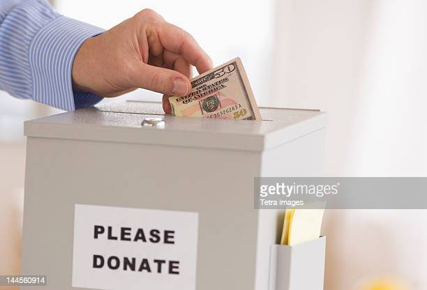 jersey city, new jersey, man's hand  putting dollars into donation box - donation stock photos and pictures