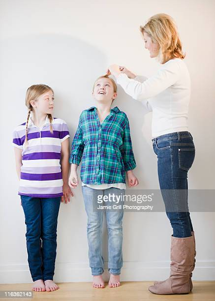 USA, Jersey City, New Jersey, mother measuring daughters' (8-11) height