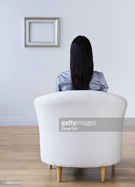 USA, Jersey City, New Jersey, rear view of woman sitting in armchair