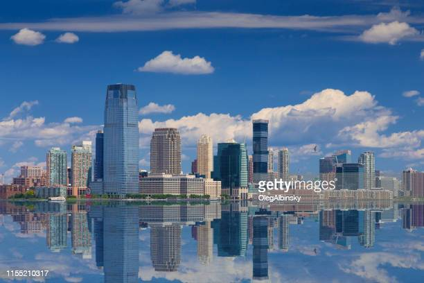 jersey city skyline with goldman sachs tower reflected in water of hudson river, new york, usa. - jersey city stock pictures, royalty-free photos & images