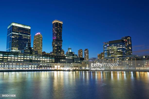 jersey city waterfront with the 'jersey city urby' skyscraper at dusk - newark new jersey stock pictures, royalty-free photos & images