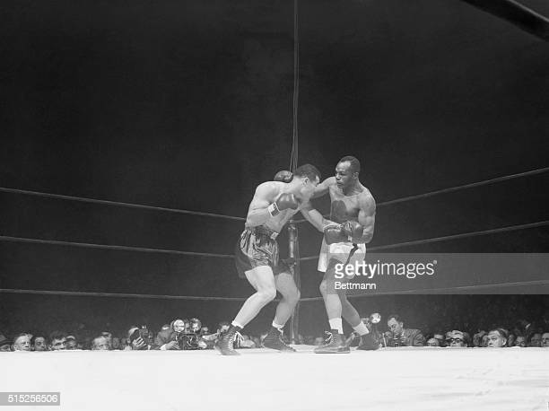 Jersey Joe Walcott , shoots a right over Joe Louis' shoulder in the first round of their scheduled 15-round title bout at Madison Square Garden, New...