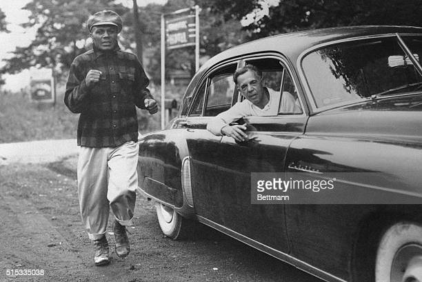 Jersey Joe Walcott, the inevitable heavyweight title challenger, keeps his legs in trim with some heavy roadwork at his training camp near...