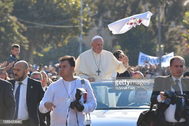 A jersey thrown by a faithful flies past Pope Francis as he waves to the faithful upon his arrival in Piazza Armerina central Sicily on September 15...