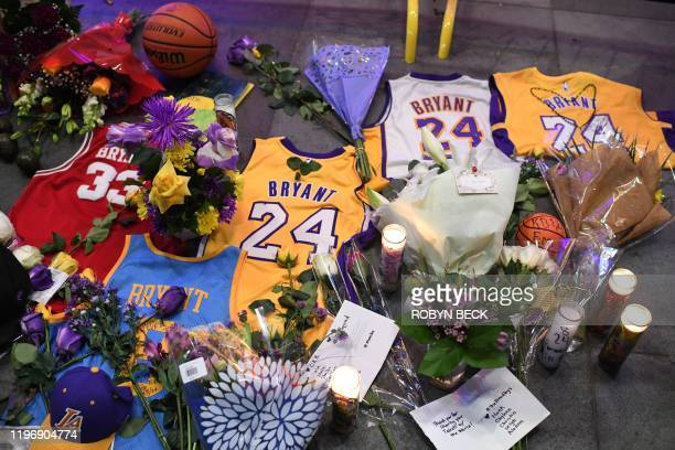 Jerseys flowers and candles are placed at a makeshift memorial as fans mourn the death of NBA legend Kobe Bryant who was killed along with his...