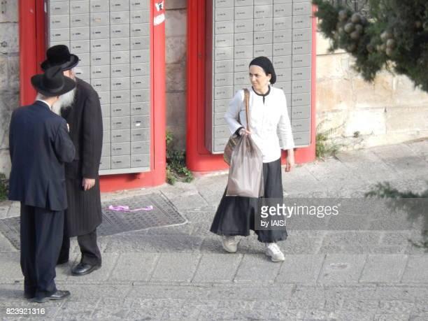 Jerusalem street scene, two elderly haredi Jews and a woman waiting