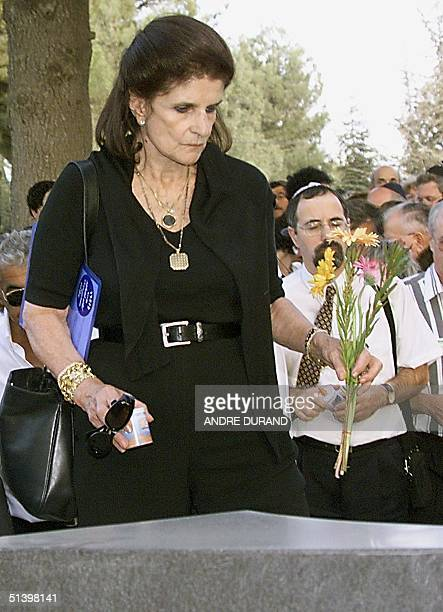Leah Rabin, widow of late Israeli Premier Yitzhak Rabin, places flowers on her husband's grave 04 November 1999 during the memorial ceremony...