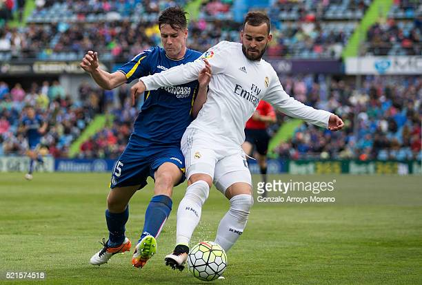 Jese Rodriguez of Real Madrid CF competes for the ball with Carlos Martin Vigaray of Getafe CF during the La Liga match between Getafe CF and Real...