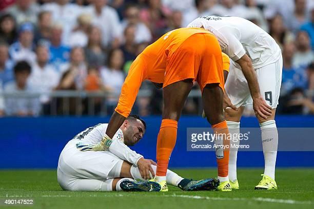 Jese Rodriguez of Real Madrid CF grimaces in pain as his teammate Karim Benzema and goalkeeper Idriss Carlos Kameni of Malaga CF assist him during...