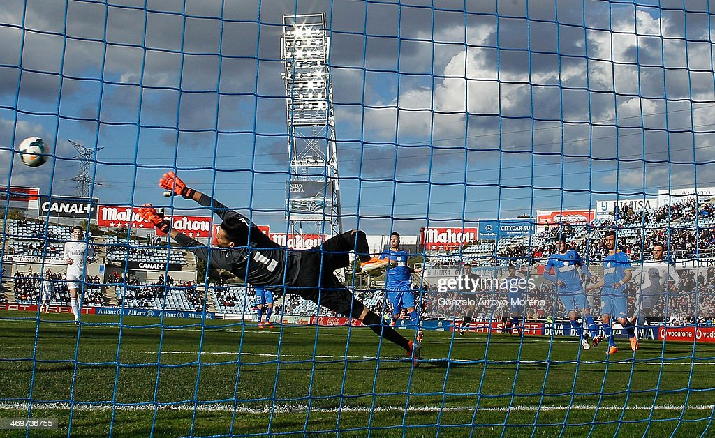Jese Rodriguez (R) of Real Madrid CF scores their opening goal through goalkeeper Miguel Angel Moya (L) of Getafe CF during the La Liga match between Getafe CF and Real Madrid CF at Coliseum Alfonso Perez on February 16, 2014 in Getafe, Spain.