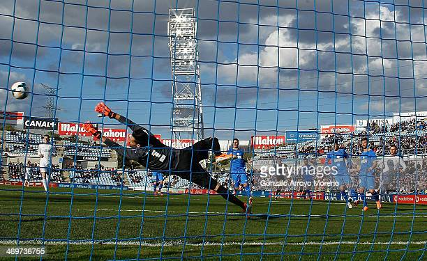 Jese Rodriguez of Real Madrid CF scores their opening goal through goalkeeper Miguel Angel Moya of Getafe CF during the La Liga match between Getafe...