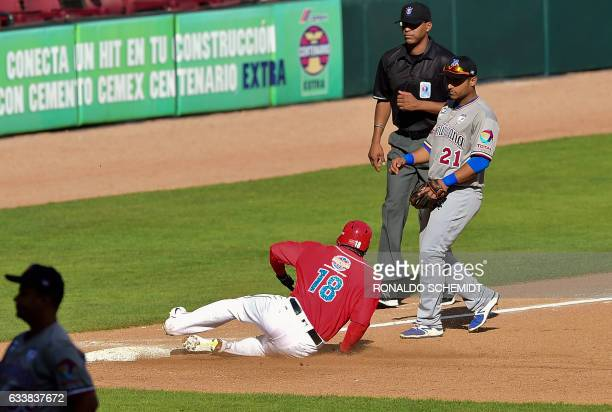 Jesmuel Valentin of Criollos de Caguas of Puerto Rico slides safe in third base during a Caribbean Baseball Series match against Tigres del Licey of...