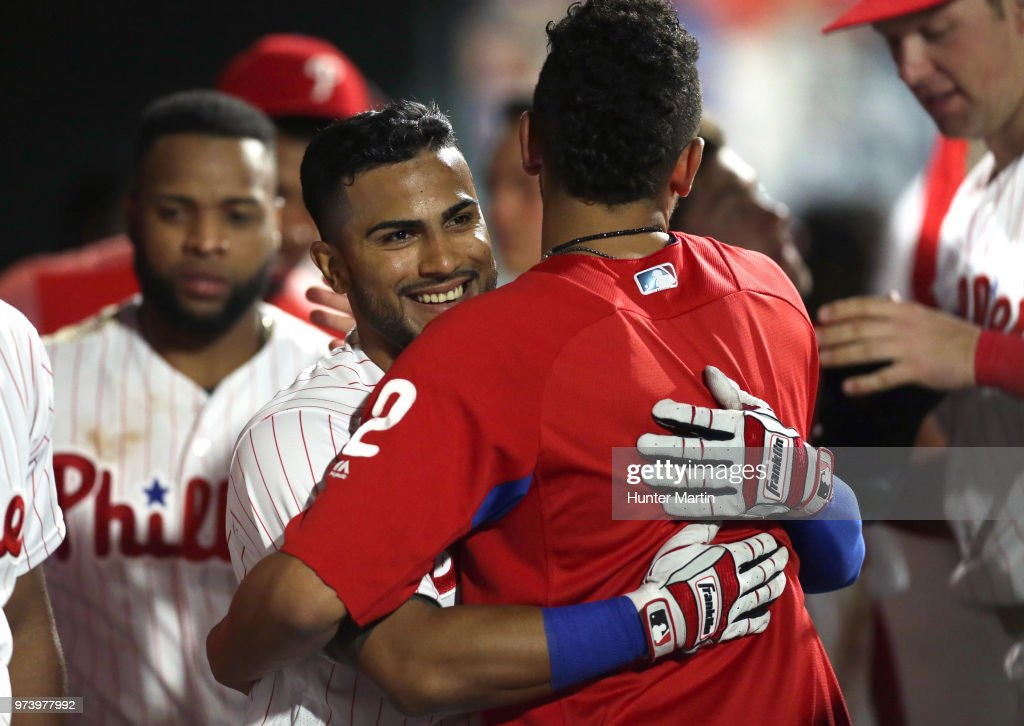 Jesmuel Valentin #9 of the Philadelphia Phillies smiles as he gets a hug from J.P. Crawford #2 after hitting his first career home run in the ninth inning during a game against the Colorado Rockies at Citizens Bank Park on June 13, 2018 in Philadelphia, Pennsylvania. The Rockies won 7-2.